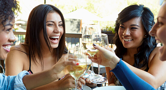 women laughing drinking wine